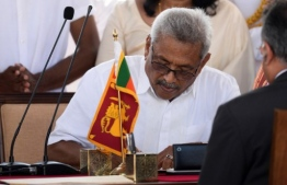 Sri Lanka's new president Gotabaya Rajapaksa signs documents during his swearing-in ceremony at the Ruwanwelisaya temple in Anuradhapura on November 18, 2019. - Sri Lanka's new president Gotabaya Rajapaksa was sworn in November 18 at a Buddhist temple revered by his core Sinhalese nationalist supporters, following an election victory that triggered fear and concern among the island's Tamil and Muslim minority communities. (Photo by Lakruwan WANNIARACHCHI / AFP)