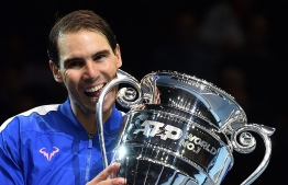 Spain's Rafael Nadal holds up the 2019 ATP Tour Year-End Number One trophy at a presentation ceremony on day six of the ATP World Tour Finals tennis tournament at the O2 Arena in London on November 15, 2019. - Spain's Rafael Nadal beat Greece's Stefanos Tsitsipas 6-7; 6-47-5. (Photo by Glyn KIRK / AFP)