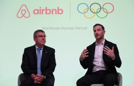 International Olympic Committee (IOC) President Thomas Bach (L) and Airbnb co-founder Joe Gebbia speak at an event in London to announce Airbnb as a leading partner of the Olympics on November 19, 2019. - Airbnb today announced a nine-year deal to become a leading partner of the Olympics, promising safe and sustainable accommodation for visitors and athletes' families. (Photo by Daniel LEAL-OLIVAS / AFP)