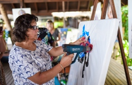 A guest attempting the plastic painting method during a workshop managed by Mbongeni Buthelezi. PHOTO: COCO PALM BODU HITHI