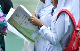 A student peruses her end-of-semester report form. FILE PHOTO: HUSSAIN WAHEED/MIHAARU