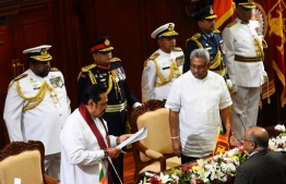 Sri Lanka's new Prime Minister Mahinda Rajapaksa (L) takes an oath as he is sworn in as finance minister in front of his brother President Gotabaya Rajapaksa (3rd R) during the ministerial swearing-in ceremony in Colombo on November 22, 2019. - Sri Lanka's new president announced holding parliamentary elections six months ahead of schedule after giving key portfolios of finance to his prime minister brother Mahinda Rajapaksa. (Photo by ISHARA S. KODIKARA / AFP)