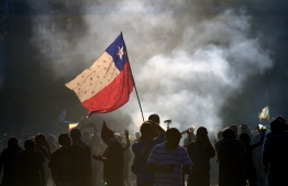 Demonstrators wave a Chile flag during a protest against the government in Santiago on November 22, 2019. - Chilean President Sebastian Pinera said on Thursday that police may have broken protocols in responding to a month of protests, and prosecutors will investigate whether they violated human rights. (Photo by Johan ORDONEZ / AFP)