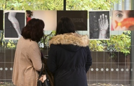 Visitors look at pictures of x-rays of a woman's broken leg (L) and a woman's broken wrist (R) displayed during the exhibition 'Invisibility is not a super power' which includes x-rays of anonymous women who arrived at the hospital's emergency service after being victims of violence, at the San Carlo Hospital in Milan on Nov. 22, 2019. - The exhibition, a combination of photographs and x-rays, is promoted on the occasion of the International day for the Elimination of Violence Against Women which takes place on November 25, 2019. (Photo by MIGUEL MEDINA / AFP)