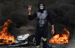 An Iraqi demonstrator flashes the victory sign at a roadblock with burning tyres in the central holy shrine city of Najaf on November 27, 2019, amid ongoing anti-government demonstrations. - Public anger over a lack of jobs triggered as of October 1 an unprecedented grassroots protest movement, Iraq's most widespread and deadly in decades, with persistent rallies demanding deep-rooted regime change across Baghdad and southern Iraq, leaving more than 350 people dead and around 15,000 wounded. (Photo by Haidar HAMDANI / AFP)
