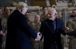 Afghan's President Ashraf Ghani shakes hands with US President Donald Trump after addressing US troops at Bagram Air Field, on November 28, 2019 in Afghanistan. (Photo by Olivier Douliery / AFP)