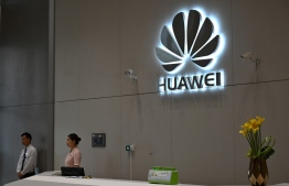 """(FILES) In this file photo taken on May 29, 2019, a company logo is displayed at a reception area at the Huawei headquarters in Shenzhen, China's Guangdong province. - US officials said on November 20, 2019, they have agreed to grant licenses to """"several"""" firms to provide components to Chinese tech giant Huawei, which faces sanctions imposed over national security concerns. A Commerce Department spokesman said the agency had granted """"narrow licenses to authorize limited and specific activities which do not pose a significant risk to the national security or foreign policy interests of the United States."""" (Photo by HECTOR RETAMAL / AFP)"""