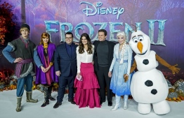 "(FILES) In this file photo taken on November 17, 2019 US actor Josh Gad (3rd L), US actor Idina Menzel (C) and US actor Jonathan Groff (3rd R) pose with people dressed as characters from the film on the red carpet as they arrive to attend the European premiere of the film ""Frozen 2"" in London. - Disney blockbuster ""Frozen 2"" held top spot at the North American box office over the Thanksgiving holiday weekend, taking in an estimated $85.2 million, industry watcher Exhibitor Relations said December 1, 2019. The animation adventure movie follows beloved characters from 2013 hit ""Frozen"" as they travel to an ancient, autumn-bound forest in search of the origin of the magical ice powers of Queen Elsa (voiced by Idina Menzel). (Photo by Niklas HALLE'N / AFP)"