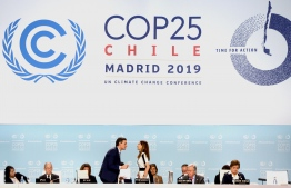 Spain's Prime Minister Pedro Sanchez (L) talks to Carolina Schmidt, Chile's Minister of Environment (R) during the UN Climate Change Conference COP25 at the 'IFEMA - Feria de Madrid' exhibition centre, in Madrid, on December 2, 2019. - Spain's Socialist government offered to host this year's UN climate conference, known as COP25, from December 2 to December 13, 2019, after the event's original host Chile withdrew last month due to deadly riots over economic inequality. (Photo by CRISTINA QUICLER / AFP)