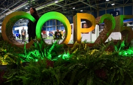 A visitors walks by the logo of the UN Climate Change Conference COP25 decorated with plants at the 'IFEMA - Feria de Madrid' exhibition centre, in Madrid, on December 2, 2019. - Spain's Socialist government offered to host this year's UN climate conference, known as COP25, from December 2 to December 13, 2019, after the event's original host Chile withdrew last month due to deadly riots over economic inequality. (Photo by GABRIEL BOUYS / AFP)