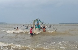 Residents help carry a wooden fishing boat into a secured area along the coast in Borongan town, Eastern Samar province, central Philippines, on December 2, 2019, as they prepare for Typhoon Kammuri. - The Philippines was braced for powerful Typhoon Kammuri as the storm churned closer, forcing evacuations and threatening plans for the Southeast Asian Games events near the capital Manila. (Photo by Alren BERONIO / AFP)