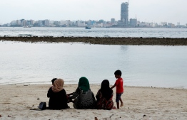 Women and children relax at the beach in Villimale'. PHOTO/UNDP