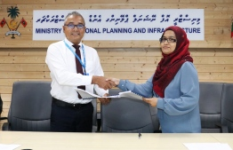 National Planning Ministry's Director Genera Harbour Fathimath Shana Farooq and MTCC's CEO Shahid Hussain Moosa sign agreement awarding the harbour construction of seven islands to MTCC, on December 10, 2019. PHOTO/PLANNING MINISTRY