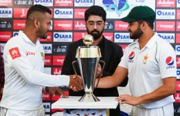 Pakistan's captain Azhar Ali (R) and his Sri Lankan counterpart Dimuth Karunaratne (L) shakes hands in front of the Test series trophy at the Pindi Cricket Stadium ahead of the first Test cricket match between Pakistan and Sri Lanka in Rawalpindi on December 10, 2019. (Photo by Aamir QURESHI / AFP)
