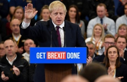 Britain's Prime Minister and Conservative party leader Boris Johnson speaks during a general election campaign event at JCB construction company in Uttoxeter,  Staffordshire, on December 10, 2019. - Britain will go to the polls on December 12, 2019 to vote in a pre-Christmas general election. (Photo by Ben STANSALL / AFP)