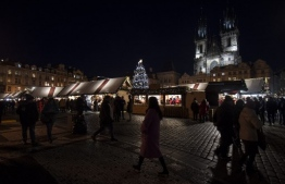 A picture taken on December 4, 2019 shows people walking past booths at a Christmas market at the Old Town Square of the Czech capital in Prague. (Photo by Michal Cizek / AFP)