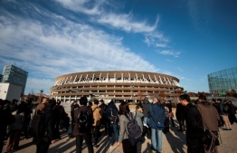 Journalists visit the National Stadium, venue for the upcoming Tokyo 2020 Olympic Games, during a media tour following the stadium's completion in Tokyo on December 15, 2019. - The Tokyo 2020 Olympics organisers on December 15 celebrated the completion of the main stadium that features use of lumber and other Japanese architectural tradition, seven months before the Opening Ceremony. (Photo by Behrouz MEHRI / AFP)