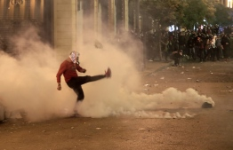 A Lebanese demonstrator kicks back a tear-gas canister during clashes with riot police in the capital Beirut on December 15, 2019. - Lebanese police clashed with anti-government protesters in Beirut late Sunday, firing tear gas to prevent them from breaching barricades near parliament, (Photo by ANWAR AMRO / AFP)