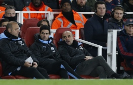 Manchester City's Spanish manager Pep Guardiola (R) and his assistant Mikel Arteta (C) watch from their seats during the English Premier League football match between Arsenal and Manchester City at the Emirates Stadium in London on December 15, 2019. (Photo by Ian KINGTON / IKIMAGES / AFP) /
