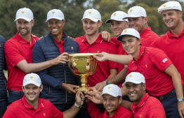 US team captain Tiger Woods (top row, 2nd L) and his teammates pose with the Presidents Cup after their win over the International Team on the final day of the Presidents Cup golf tournament in Melbourne on December 15, 2019. (Photo by SIMON BAKER / AFP) /