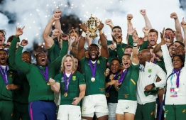 (FILES) In this file photograph taken on November 2, 2019, South Africa's flanker Siya Kolisi (C) lifts the Webb Ellis Cup as he celebrates with teammates after winning the Japan 2019 Rugby World Cup final match between England and South Africa at the International Stadium Yokohama in Yokohama. - The Springboks delighted the 'Rainbow Nation' by overcoming an opening pool defeat by New Zealand to claim a third World Cup title after previous successes in 1995 and 2007. Reinvigorated by coach Rassie Erasmus, a multi-cultural team skippered by the country's first black skipper, Siya Kolisi, beat Japan and Wales in the knock-out phase to set up a final against England, a game they won easily, 32-12, to claim the Webb Ellis trophy. The Springboks' gameplan was not a tough one to work out: forward power and a crashball midfield alongside a solid kicking game to ensure maximum pressure on opponents. When they cracked, the playmakers set outstanding flying wingers Makazole Mapimpi and Cheslin Kolbe loose. It could be argued that the Boks weren't even the best side at the World Cup, but under the ever-entertaining Erasmus, they made sure they kept their nerve and took their chances. (Photo by Odd ANDERSEN / AFP)
