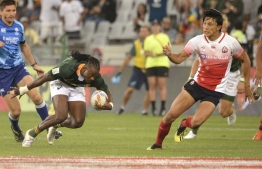 South Africa's Seabelo Senatla (L) is challenged by Japan's Chihito Matsui (R) during  the HSBC World Rugby Sevens Series men's rugby match between South Africa and Japan at the Cape Town Stadium in Cape Town, on December 13, 2019. (Photo by RODGER BOSCH / AFP)