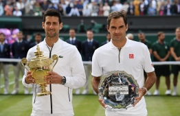 (FILES) In this file photo taken on July 14, 2019 Serbia's Novak Djokovic (L) poses with the winner's trophy and Switzerland's Roger Federer (R) holds the runners up plate during the presentation after the men's singles final on day thirteen of the 2019 Wimbledon Championships at The All England Lawn Tennis Club in Wimbledon, southwest London. (Photo by Ben STANSALL / AFP) / RESTRICTED TO EDITORIAL USE