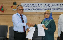 COO of MTCC Shahid Hussain Moosa exchanges agreement with Director General of National Planning Ministry Fathimath Shaanaa Faarooq; the planning ministry awarded the project to upgrade Isdhoo's harbour to MTCC. PHOTO/PLANNING MINISTRY