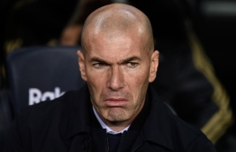 "Real Madrid's French coach Zinedine Zidane looks on during the ""El Clasico"" Spanish League football match between Barcelona FC and Real Madrid CF at the Camp Nou Stadium in Barcelona on December 18, 2019, (Photo by Josep LAGO / AFP)"