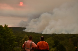 Residents watch a large bushfire as seen from Bargo, 150km southwest of Sydney, on December 19, 2019. - A state of emergency was declared in Australia's most populated region on December 19 as an unprecedented heatwave fanned out-of-control bushfires, destroying homes and smothering huge areas with a toxic smoke. (Photo by Peter PARKS / AFP)