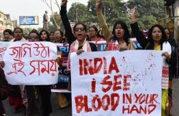 Female demonstrators hold placards and shout slogans during a protest against India's new citizenship law in Guwahati on December 21, 2019. - Thousands of people joined fresh rallies against a contentious citizenship law in India on December 21, with 20 killed so far in the unrest. (Photo by Biju BORO / AFP)