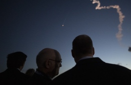 This handout photo released by NASA shows Florida Gov. Ron DeSantis (R), left, Tory Bruno, president and CEO of United Launch Alliance, and NASA Administrator Jim Bridenstine watch as a United Launch Alliance Atlas V rocket with Boeing's CST-100 Starliner spacecraft onbaord launches from Space Launch Complex 41 at Cape Canaveral Air Force Station, Friday, Dec. 20, 2019, from NASA's Kennedy Space Center in Florida. The uncrewed Orbital Flight Test launched at 6:36 a.m. EST and is Starliner's maiden mission to the International Space Station for NASA's Commercial Crew Program. The mission will serve as an end-to-end test of the system's PHK KOWSKY / NASA / AFP