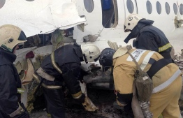 This handout picture taken on December 27, 2019 and released by Kazakhstan's emergencies committee shows rescuers working at the site of a passenger plane crash outside Almaty. - At least 15 people died and dozens were injured on December 27, 2019 when a passenger plane carrying 100 people crashed shortly after takeoff from Kazakhstan's largest city and slammed into a house, state media reported. (Photo by HO / Kazakhstan's emergencies committee / AFP) /