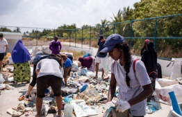 Rai rummages through garbage participating in a clean-up activity hosted on a local island. PHOTO: ALICIA WANER