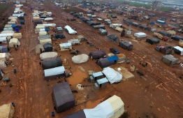 An aerial photograph shows tents sheltering Syrians who fled ongoing battles in the southern and eastern coutryside of the Idlib province, surrounded by mud caused by heavy rain, in a camp for displaced people near Sarmada near the border with Turkey in the northern part of the province on December 29, 2019. (Photo by Aref TAMMAWI / AFP)