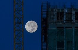 The moon is seen near a construction site in Kuala Lumpur on December 13, 2019. (Photo by Mohd RASFAN / AFP)