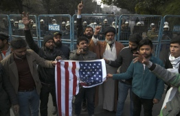 """Protesters hold a burned US flag as they shout slogans during a demonstration near the US consulate following a US airstrike that killed top Iranian commander Qasem Soleimani in Iraq, in Lahore on January 3, 2020. - A US strike killed top Iranian commander Qasem Soleimani at Baghdad's international airport On January 3, dramatically heightening regional tensions and prompting arch enemy Tehran to vow """"revenge"""". (Photo by ARIF ALI / AFP)"""