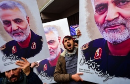 """Protesters hold pictures of Iranian commander Qasem Soleimani, during a demonstration outside the US consulate in Istanbul, on January 5, 2020, two days after top Iranian commander Qasem Soleimani was killed by a US drone strike. - A US drone strike killed top Iranian commander Qasem Soleimani at Baghdad's international airport on January 3, dramatically heightening regional tensions and prompting arch enemy Tehran to vow """"revenge"""". (Photo by Yasin AKGUL / AFP)"""