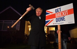 "Britain's Prime Minister and Conservative party leader Boris Johnson poses after hammering a ""Get Brexit Done"" sign into the garden of a supporter, with a sledgehammer as he campaigns with his team in Benfleet, east of London on December 11, 2019, the final day of campaigning for the general election. - Britain will go to the polls tomorrow to vote in a pre-Christmas general election. PHOTO: BEN STANSALL / POOL / AFP"