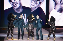 Twin brothers Dean and Dan Caten perform with singers during the presentation of the men's fall/winter 2020/21 fashion collection they designed for Dsquared2, which celebrates its 25th anniversary, in Milan on January 10, 2020. (Photo by Miguel MEDINA / AFP)