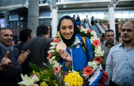 (FILES) In this file photo taken on August 26, 2016 Keivan Alizadeh (R) the father of Kimia Alizadeh who became the first Iranian woman ever to win an Olympic medal, shows her medal upon her arrival at Imam Khomeini International Airport in tcapital Tehran. (Photo by peyman / ISNA / AFP)