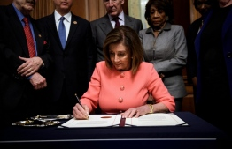 US Speaker of the House Nancy Pelosi signs the Articles of Impeachment against US President Donald Trump at the Rayburn Room on Capitol Hill January 15, 2020, in Washington, DC. - The US House of Representatives voted Wednesday to transmit articles of impeachment against President Donald Trump to the Senate, opening the way for the historic trial of the 45th president for abuse of power. (Photo by Brendan Smialowski / AFP)