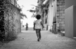 A child running on the streets of Kanduhulhudhoo, Gaafu Alif Atoll. PHOTO: NISHAN ALI/ MIHAARU