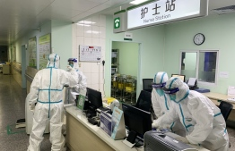 This photo taken on January 22, 2020 shows medical staff members wearing protective suits at the Zhongnan hospital in Wuhan in China's central Hubei province. - China banned trains and planes from leaving Wuhan at the centre of a virus outbreak on January 23, seeking to seal off its 11 million people to contain the contagious disease that has claimed 17 lives, infected hundreds and spread to other countries. (Photo by STR / AFP) /