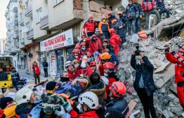 Rescue workers evacuate an injured woman from the rubble of a building after an earthquake in Elazig, eastern Turkey, on January 25, 2020. - Rescue workers raced against time on January 25 to find survivors under the rubble after a powerful earthquake claimed 22 lives and left more than 1,200 injured in eastern Turkey. The magnitude 6.8 quake struck in the evening of January 24, with its epicentre in the small lakeside town of Sivrice in Elazig province, and was felt across neighbouring countries. (Photo by BULENT KILIC / AFP)