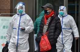Medical staff wearing clothing to protect against a previously unknown virus walk outside a hospital in Wuhan on January 26, 2020, a city at the epicentre of a viral outbreak that has killed at least 56 people and infected nearly 2,000. - China on January 26 expanded drastic travel restrictions to contain the viral contagion, as the United States and France prepared to evacuate their citizens from the quarantined city at the outbreak's epicentre. (Photo by Hector RETAMAL / AFP)