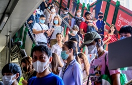 People with face masks arrive at a BTS Sky train station in Bangkok on January 27, 2020. - Thailand has detected eight Coronavirus cases so far -- three of whom are receiving treatment in hospital and five of whom have been discharged, according to a statement from Health Minister Anutin Charnvirakul. (Photo by Mladen ANTONOV / AFP)