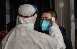 A security personnel wearing protective clothing to help stop the spread of a deadly virus which began in Wuhan, checks the temperature of a man at a subway station entrance in Beijing on January 27, 2020. (Photo by NICOLAS ASFOURI / AFP)