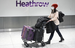 "Passengers wear face masks as the push their luggage after arriving from a flight at Terminal 5 of London Heathrow Airport in west London on January 28, 2020. - Chinese President Xi Jinping said Tuesday the country was waging a serious fight against the ""demon"" coronavirus outbreak and pledged transparency in the government's efforts to contain the disease. (Photo by DANIEL LEAL-OLIVAS / AFP)"