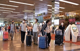 Travellers wear protective facemasks at the departure hall of Changi international airport in Singapore on January 30, 2020. - Singapore flew home 92 of its citizens from Wuhan, the Chinese city at the centre of a deadly virus outbreak on a chartered plane on January 30, the foreign ministry said in a statement. PHOTO: ROSLAN RAHMAN / AFP